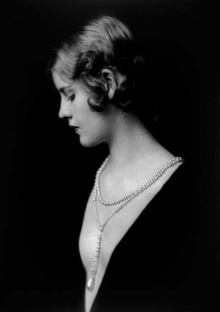 A photo of Caja Eric in fancy dress and a pearl necklace.