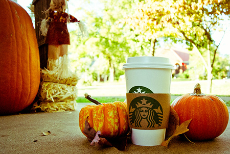A Starbucks cup surrounded by pumpkins outdoors.  Source: Flickr - Denise Mattox
