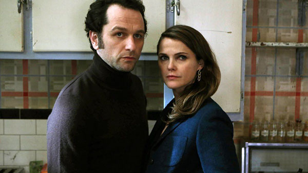 Photo of The Americans. Matthew Rhys (left) and Keri Russell (right) are standing in their kitchen very concerned.
