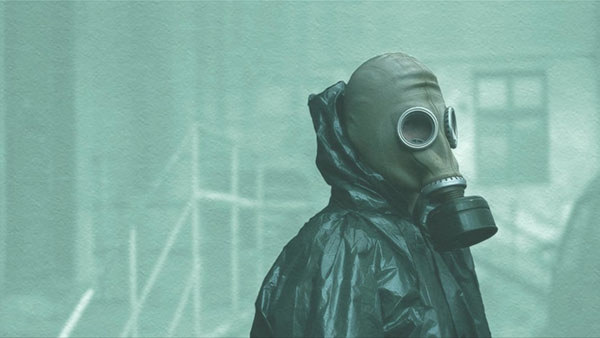 Screen shot of a man in a gas mask with black radiation gear from the show Chernobyl