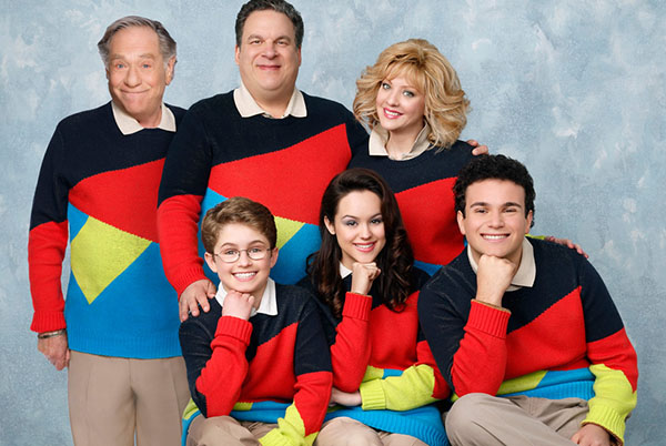 Photo of the Goldbergs. They are all in the same matching geometric bold coloured sweater with the adults standing and the kids sitting on a bench not visible to the camera. The kids have their right fist under their chins with their right leg crossed over their other leg.