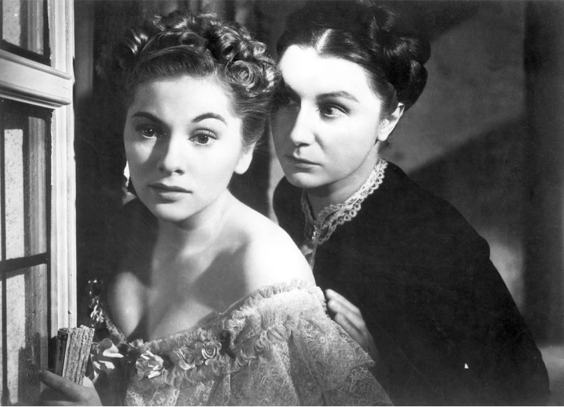 Screenshot of Rebecca (1940). Ms Dnavers is glaring at Mrs. de Winter standing at a door.