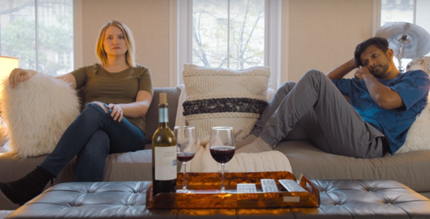 Brittany sitting on the couch with Jern. Two adults drinking wine on a couch. Woman sitting upright, fully dressed with legs crossed. Man with legs and feet on the couch slouching on the couch.