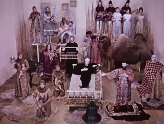 Screenshot of poet's dream. From the back: knights on a table, a chorus and lute players, man holding a swan, large woman holding a baby in purple, man holding a cage, man holding robe to a camel. From the front left: a calf, a woman in beige holding a candle and a baby, two woman knelling holding a baby. From the right: man standing on rug with plaid shroud, man with right arm extended outwards and left arm on his chest standing on a rug. Centre: Woman in black with a crown laying down extending her left arm on a bed in front of a bell.