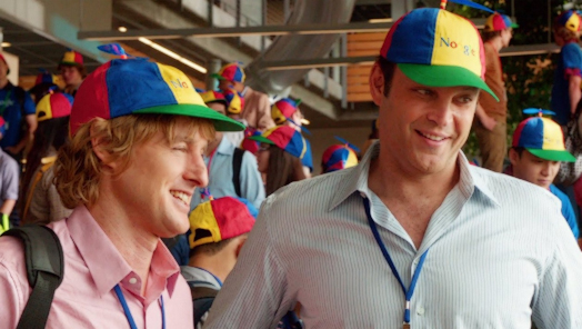 Screenshot of The Internship. Two middle aged men with Google hats enjoy a conversation with someone off-screen.