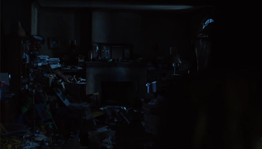 Screenshot of the dead painter's apartment. Messy apartment with books, papers and paint everywhere.