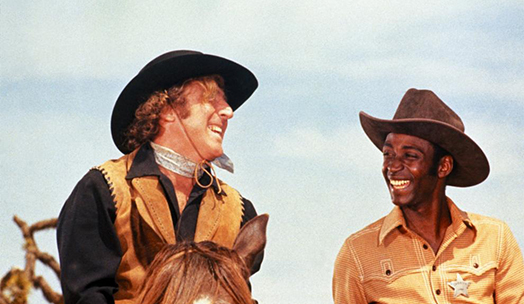 Screen shot of Blazing Saddles. From the left: Jim a.k.a The Waco Kid and Sheriff Bart are laughing riding horses on a sunny day.