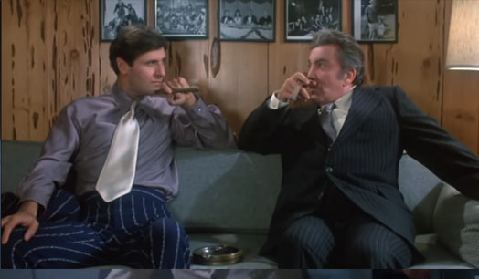 Screenshot of King Kaiser and the mob boss on the couch during a lawyer visit at the office. King Kaiser is copying the mob boss's actions beside him by holding the cigar with his elbow bent on the head of the couch and the cigar near his mouth. Kaiser is looking at the mob boss smugly while the mob boss is looking at Kaiser with curiously at his actions.