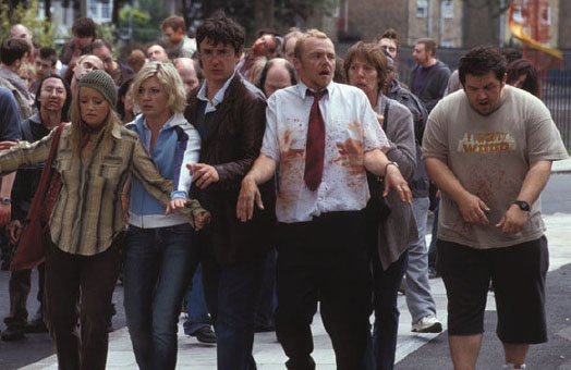 A group of men and women walking in a crowd of zombies.They have a combination of the look of concern and zombie faces. A man in a red tie has his white shirt painted in red dye.